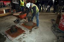 A precast concrete plant employee performs a slump flow test on Self-Consolidating Concrete (SCC).