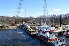 Towboats transported concrete trucks on barges to the construction sites of two of the five tower foundations for the CapX2020 Mississippi River crossing, a 1.3-mile transmission line segment from near Wabasha, Minnesota, to Alma, Wisconsin.