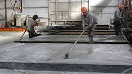 Plant employees finish the unformed surfaces of the wet cast concrete products.