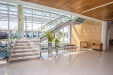 An open staircase to the second floor highlights a two-story atrium in the clinic's main lobby.